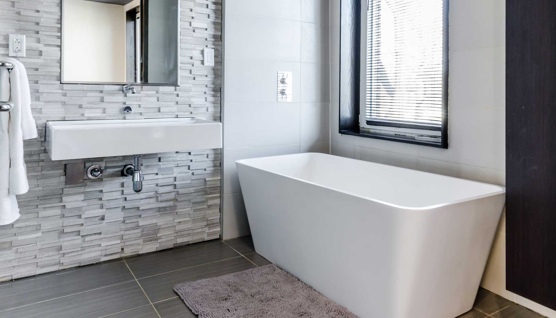 White bathub in bathroom under window with white blinds sits beside modern white sink with a grey tile backsplash