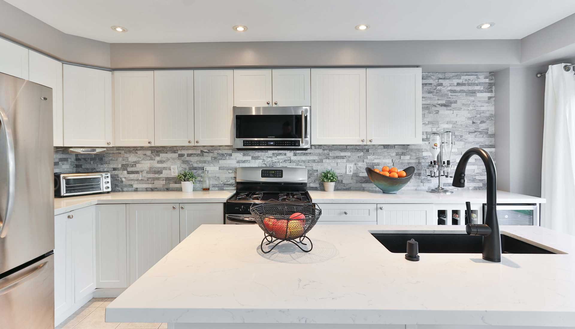 White kitchen island with black sink and faucet sits in front of a white kitchen countertop with white cabinetry and a black stove