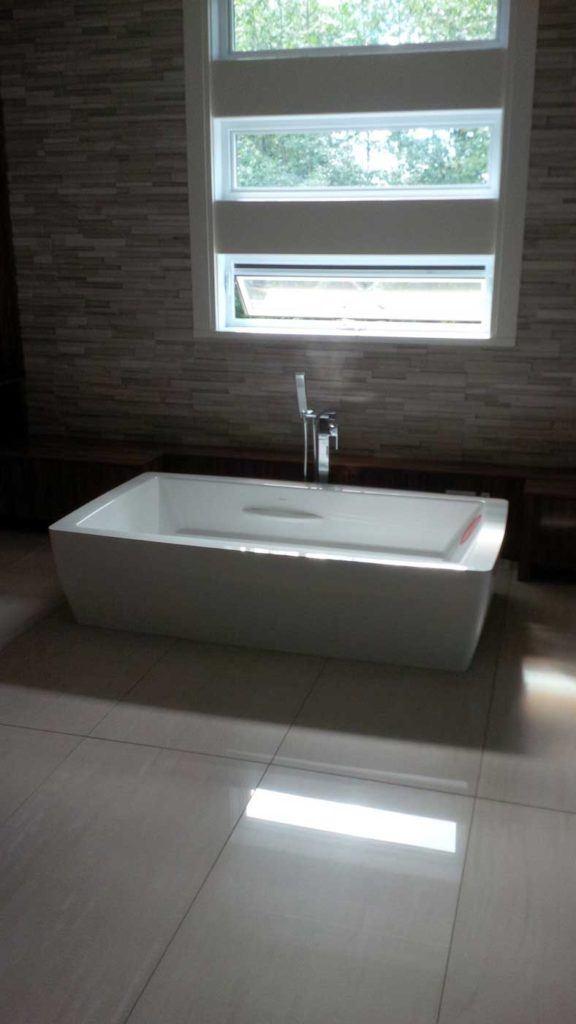 White square sink, still uninstalled, sits in bathroom under a window