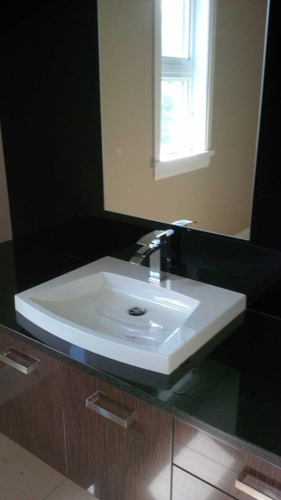 White bathroom sink sits on black countertop with mirror above