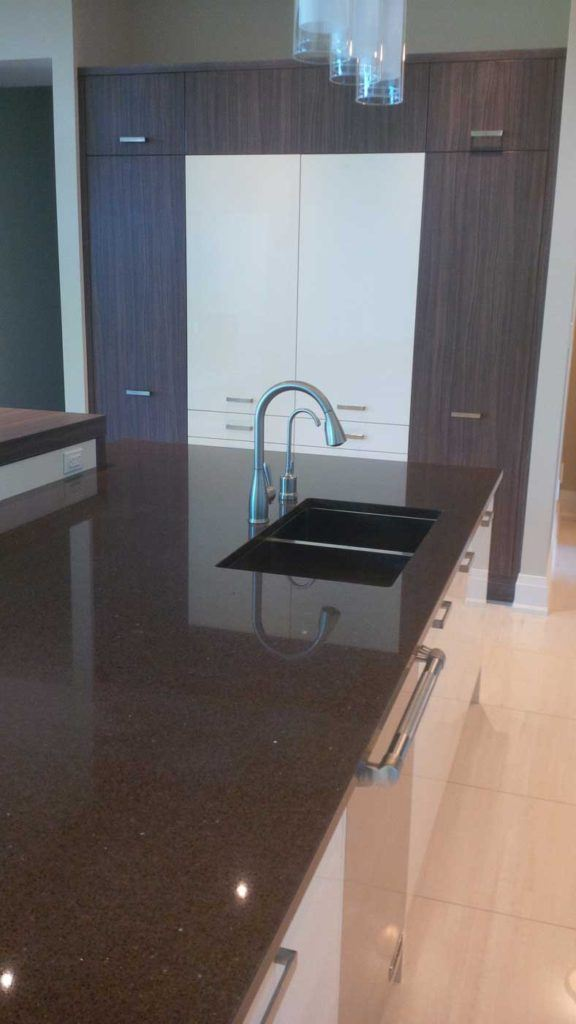 Double-sink in a kitchen island with black countertop