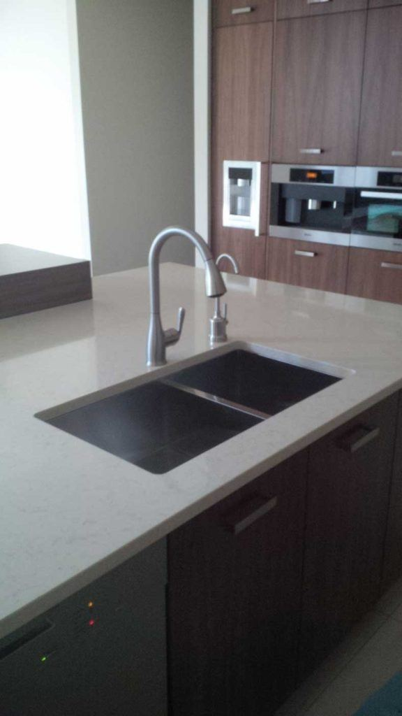 Double-sink in a kitchen-island with a white countertop