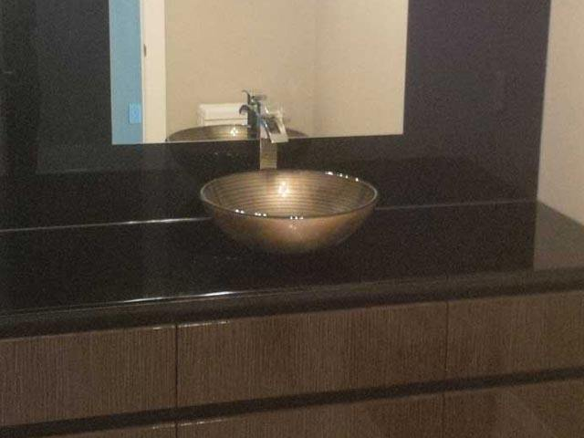 Bathroom sink bowl on brown countertop with brown-framed mirror above