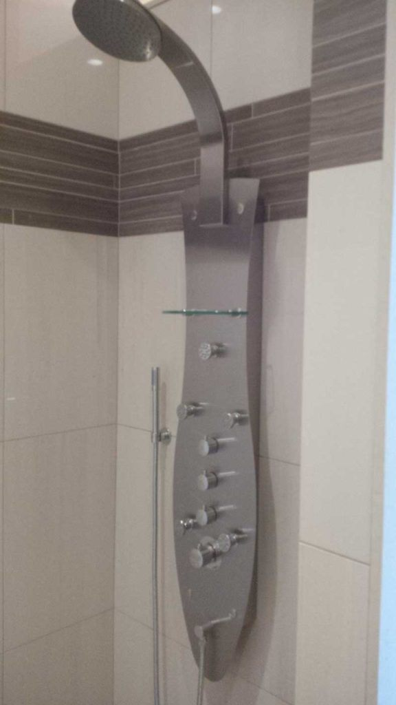 Metal shower faucet set in a stand-up shower with brown & beige tiles.