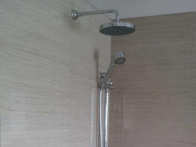 Stand-up shower faucet overhang and handheld faucet unit with beige walls