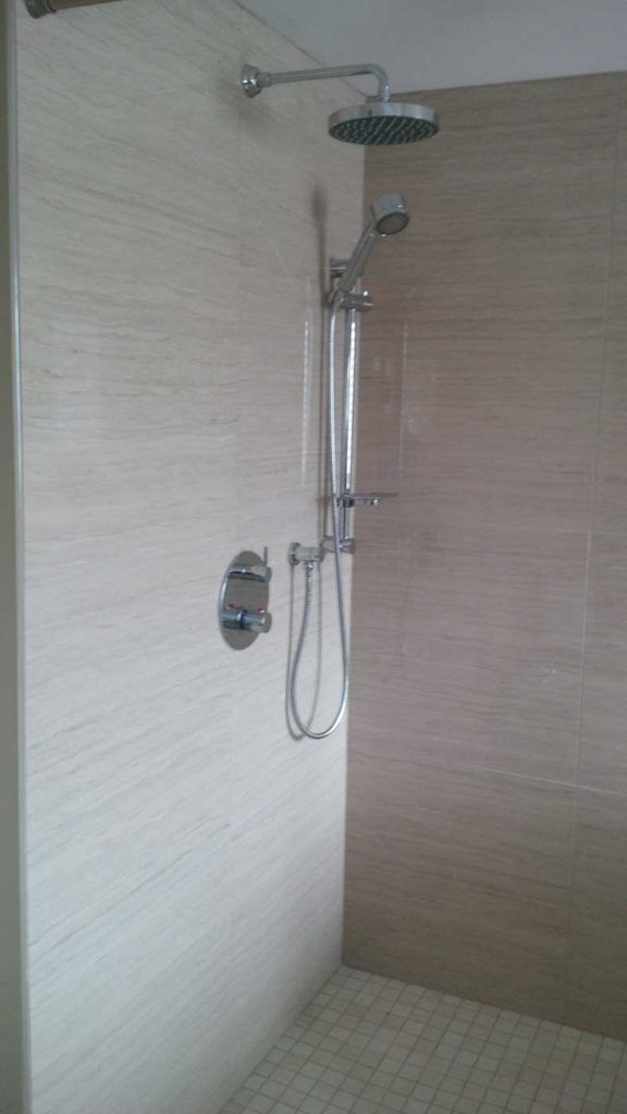 Shower faucet in a stand-up shower with beige walls and beige floor tiles