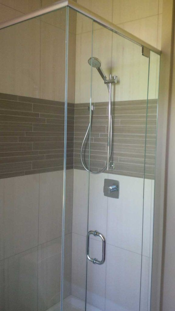 Stand-up shower with glass door and beige & brown tiles