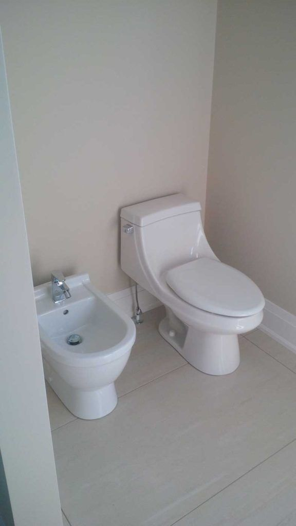 White bidet to the left of a white toilet in a white bathroom