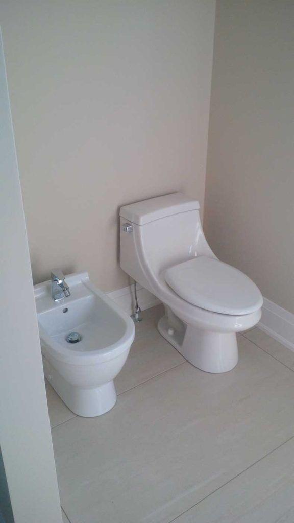 White bidet to the left of a white toilet in a white bathroom